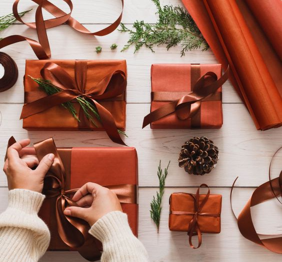Gift wrapping. Packaging stylish christmas present boxes in maroon paper decorated with satin ribbon bows. Christmas and winter holidays concept, top view, hands making bow